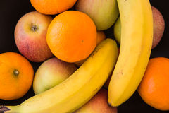 Selection of fruit in a black bowl from above. Stock Photography