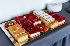 Selection of fruit cake slices with strawberry, kiwi, jelly, apple on silver platter and blurred background stock images