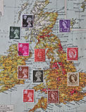 Selection of GB Postage stamps over old map.  Stock Image