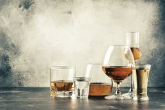 Selection of hard strong alcoholic drinks in big glasses and small shot glass in assortent: vodka, cognac, tequila, brandy and royalty free stock photos