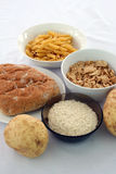 Selection of healthy carbohydrates. A selection of carbohydrates; rice, bread, potatoes, cereal and pasta stock image