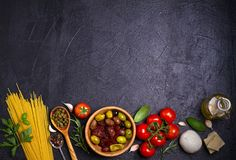 Selection of healthy food. Italian food background with spaghetti, mozzarella parmesan cheese, olives, tomatoes and rosemary. Vegetarian food banner. overhead Stock Photos