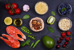 Selection of healthy and good for heart food. Healthy food concept with salmon, fresh vegetables, fruits and ingredients for cooki Stock Photos