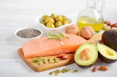 Selection of healthy unsaturated fats, omega 3 - fish, avocado, olives, nuts and seeds. Selection of healthy unsaturated fats, omega 3 - fish, avocado, olives royalty free stock photography