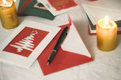 Selection of home made Christmas cards. On a table with envelopes, candles and a ink fountain pen Stock Image
