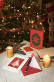 Selection of home made Christmas cards. On a table with envelopes, candles and a ink fountain pen Stock Images