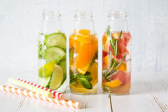 Selection of infused water in glass bottles, rustic wood background Stock Images