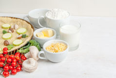 Selection of ingredients for quiche lorraine. The selection of ingredients for the preparation of traditional French dishes quiche lorraine, on white wooden Stock Image