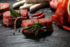 Selection of marinaded meat for bbq grilling with herbs on table stock image