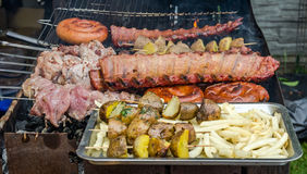 Selection of meat grilling over the coals on a portable barbecue with spicy sausages, beef kebabs and racks of ribs, outdoors Stock Photos