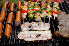 Selection of meat grilling over the coals with spicy sausages, bacon and chicken skewers Stock Photo