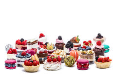 Selection of miniature cakes, macrons, cupcakes and treats. Isolated Stock Image