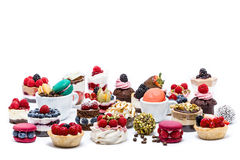 Selection of miniature cakes, macrons, cupcakes and treats. Isolated Royalty Free Stock Photo