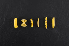 Selection of pasta uncooked, isolate on black slate background Stock Images