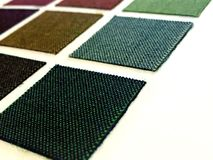 Fabric designs. A selection of plain fabric designs of different colors stock photos