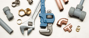 Selection of Plumbers Tools and Plumbing Materials. Various plumbers tools and plumbing materials including copper pipe, elbow joint, wrench and spanner. shot on stock photography