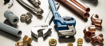 Selection of Plumbers Tools and Plumbing Materials. Various plumbers tools and plumbing materials including copper pipe, elbow joint, wrench and spanner. shot on stock images