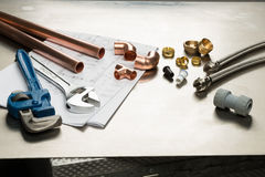 Selection of Plumbers Tools and Plumbing Materials. Various plumbers tools and plumbing materials including copper pipe, elbow joint, wrench and spanner. shot on Stock Photo