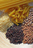 Selection of pulses. A selection of pulses set on an oval wooden plate consisting of Rice, lentils, pasta, chick peas stock image