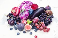 Selection of purple foods. Fruits, berries and vegetables on white background. Purple or eat by color diet concept. Copy space stock photography