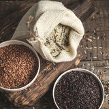 Selection of red, black and mixed rice on an old wooden background Royalty Free Stock Images
