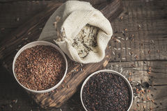 Selection of red, black and mixed rice on an old wooden background.Top view with copy space Stock Photography
