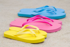 Selection of rubber flip flops in multiple colors on beach Stock Image