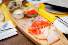 Selection of sea fish in the restaurant. Selection of fish including soft-salted pike perch, sea trout, smoked butterfish, salmon caviar, lamprey Royalty Free Stock Image