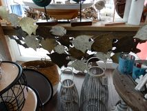 Selection of seaside in a shop. Selection of seaside or coast related gift items in a shop display glassware decoration fish wood basket lamps table boot Stock Photo