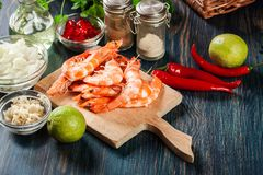Selection of shrimp ready for frying with onion, garlic, chili and lime on cutting board. Side view Stock Images