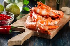 Selection of shrimp ready for frying with onion, garlic, chili and lime on cutting board. Side view Stock Photography