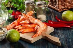 Selection of shrimp ready for frying with onion, garlic, chili and lime on cutting board Stock Images