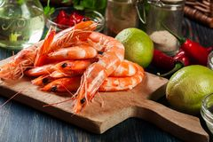 Selection of shrimp ready for frying with onion, garlic, chili and lime on cutting board Stock Photography