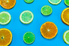 Selection of slices of citrus fruit on a bright high contrast turquoise background. Horizontal view of slices of citrus fruit on a bright high contrast turquoise royalty free stock photo