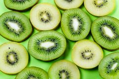 Selection of slices of yellow and green kiwi fruit on a bright high contrast green background. Horizontal view of slices of golden yellow and green kiwi fruit on stock images