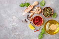 Selection of spices and herbs - garlic, salt, pink, green and black pepper, lemon, Basil, olive oil. Ingredients for cooking. Stock Photos
