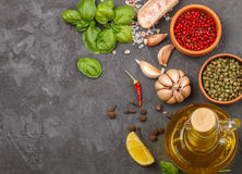 Selection of spices and herbs - garlic, salt, pink, green and black pepper, lemon, Basil, olive oil. Ingredients for cooking. Royalty Free Stock Photo