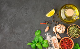 Selection of spices and herbs - garlic, salt, pink, green and black pepper, lemon, Basil, olive oil. Ingredients for cooking. Stock Photography