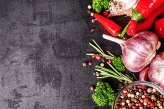 Selection of spices herbs and greens. Ingredients for cooking. Food background on black slate table.  stock photo