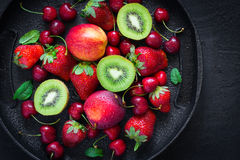 Selection. of summer berries and fruits on a black plate. Top vi stock images