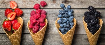 Selection of summer berries in ice cream cones. On rustic background. Healthy dessert, lifestyle Stock Photo
