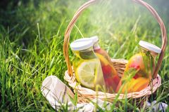 Selection of summer lemonades. Basket on the meadow with refreshing drinks stock photos