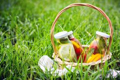Selection of summer lemonades. Basket on the meadow with refreshing drinks stock images
