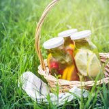 Selection of summer lemonades. Basket on the meadow with refreshing drinks stock photo