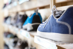 Selection of Summer Season Footwear in Retail Shop. Selection of Summer Season sporty and travel Footwear on wooden Wall of Retail Shop stock image