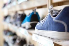 Selection of Summer Season Footwear in Retail Shop. Selection of Summer Season sporty and travel Footwear on wooden Wall of Retail Shop Stock Image