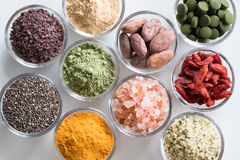 Selection of superfoods on a white background. Goji berries, chlorella, young barley powder, dulse seaweed, maca, chia seeds, turmeric, himalayan sea salt royalty free stock photography