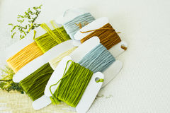 Selection of threads for embroidery in natural colors. Fragment of embroidery and a set of threads for embroidery in natural colors. Handicraft. Selective focus royalty free stock image
