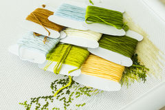 Selection of threads for embroidery in natural colors. Fragment of embroidery and a set of threads for embroidery in natural colors. Handicraft. Selective focus royalty free stock photo