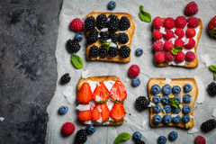 Selection of toasts with cheese peanut butter and berries Stock Photos